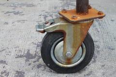 Rusty steel scaffold wheel close up on concrete floor. Rusty steel scaffold wheel close up Stock Image