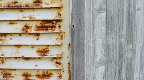 Rusty steel shutter and wooden wall. Old white pained rusty steel shutter and old gray wooden wall Stock Photos