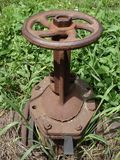 Rusty steel water tap in the green and dry grass Stock Photo