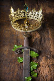 Rusty sword and golden crown. Antique medieval sword and golden crown decorated with ivy Stock Images