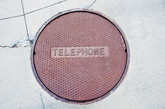 Rusty telephone manhole cover in cracked pavement Stock Photos