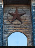 Rusty Texas star hanged on wooden building facade. Wooden cabin in Texas stock image