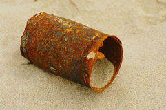 Rusty tin can on beach. An exceedingly old and rusty tin can in complete decay on a beach, filled with sand Royalty Free Stock Image