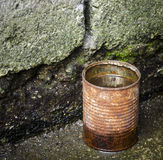 Rusty tin can with water. In a dirty corner. This can be a good concept on drinking water, danger of unprocessed water, dirty environment, etc Royalty Free Stock Images