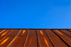 Rusty Tin Metal Roof & Clear Blue Sky. Rusty metal roof on an old country building with a clear, late afternoon, blue sky in the background. Lots of copy space Stock Photos