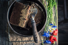 Rusty tools for beekeeping with honeycombs, hats and honey. On old wooden table stock image