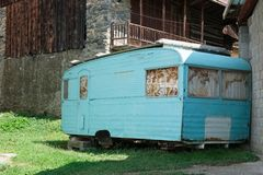 Rusty trailer leaning against a house Royalty Free Stock Photo