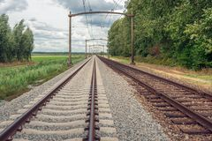Rusty train tracks with overhead lines in the Netherlands. Dutch landscape with rusty train tracks with overhead lines. It is a cloudy day in the Dutch summer stock photo
