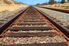 Rusty train tracks with sandstone. Looking straight on to the train tracks, with sandstone on either side of the tracks. The train tracks lead to a vanishing Stock Image