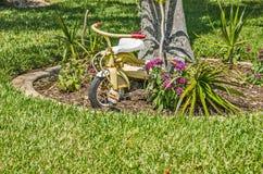 Rusty Tricycle Decorating a la yarda foto de archivo libre de regalías