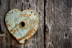 Rusty trim on keyhole  as heart on old wooden door. Stock Photo