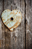 Rusty trim on keyhole as heart on old wooden door. Vertical shot Stock Photography