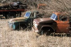 Rusty Trucks. Two old pickup trucks left to rust in a field Stock Photos