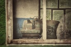 Rusty turning machine in old factory. Old abandoned factory, broken glass in windows and rusty turning lathe Royalty Free Stock Image