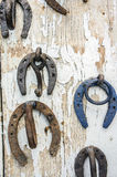 Rusty upside down horseshoes on wood panel Royalty Free Stock Photos