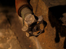 Rusty Valve. A rusty valve taken with light from a flashlight in a furnace room stock image