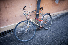 Rusty vintage bicycle near the concrete wall Royalty Free Stock Image