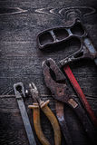 Rusty vintage hacksaw nippers pliers on wooden board constructio Royalty Free Stock Photo