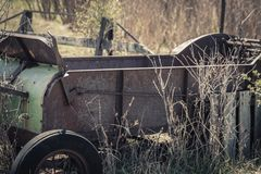 Rusty Vintage Hay Baler Cart Farm Decor. An old vintage hay baler cart sits in a farm field surrounded by grass and bushes. It is now being used as lawn decor stock image