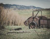Rusty Vintage Hay Baler Cart. An old vintage hay baler cart sits abandoned on a farm surrounded by a grassy field, old junk and dried brush royalty free stock image