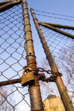 Rusty vintage metallic padlock hangs on wire netting gate Stock Photo