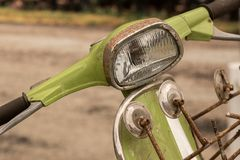 Rusty vintage mod green scooter bike handlebar, mirrors and headlamp. Rusted chrome surround of a glass headlight on a classic retro motorbike royalty free stock images