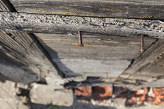 Rusty vintage nails in wooden wall and blurred red bricks. Rusty nails in wooden wall outdoors Royalty Free Stock Photos
