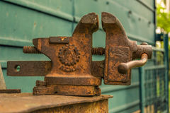 Rusty vise. Old rusty vice on a metal workbench with green metal wall behind Stock Image