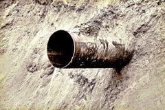 Rusty water drain pipe on slope taken closeup. Royalty Free Stock Image