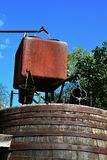 Rusty water pipes, square shaped rusty flow-through water reservoir and water distribution mechanism with two wooden buckets Stock Photography