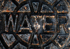 Rusty Water Sign. Photo of a rusty city water hole cover royalty free stock image