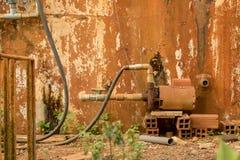 Rusty Water Turbine Generator - möglig skalad trädgård för betongväggtexturtappning arkivbilder