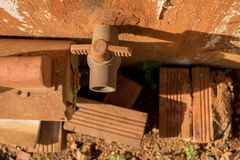 Rusty Water Turbine Generator and Vintage Old PVC Valve with Plastic Pipeline - Moldy Concrete Wall Texture - Dirty Bricks on stock photos