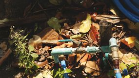 Rusty Water Valve e tubulação na terra molhada do jardim com folhas, grama e madeira secas imagem de stock royalty free
