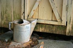Rusty watering can and shed Royalty Free Stock Photo