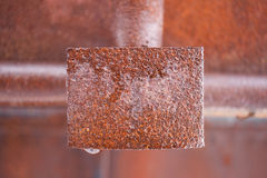 Rusty wet metal rectangular plate in middle of frame. royalty free stock images