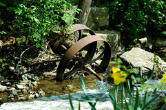 Rusty Wheel. In background with yellow daffodil in foreground royalty free stock photo