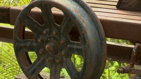 A rusty wheel of an old rail push trolley carriage