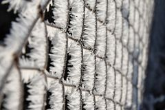 Rusty wire fence covered with frost and hoarfrost. Royalty Free Stock Photography