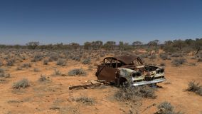 Rusty wreck of crashed car in the middle of desert warning to inattentive drivers, Stuart Highway, Australia royalty free stock photos