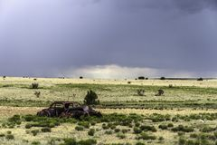 Rusty wreckage of a car. Old rusty wreckage of a car in a field alongside the road 66, New Mexico Stock Photos