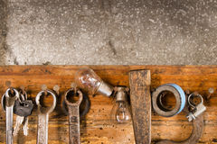 Rusty wrenches, adhesive tape, an awl, a light bulb, a collar on an old wooden below Royalty Free Stock Photo