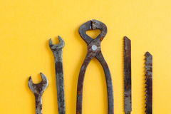 Rusty wrenches pliers saw blades on yellow paper. Vintage iron hand tools instrument for service and repair works. Stock Photos