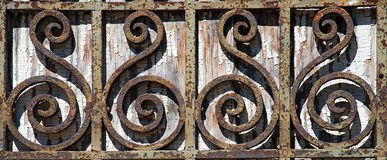 Rusty Wrought Iron Fence Detail. Rust and chipping paint add grungy detail to this old wrought iron gate Stock Photo