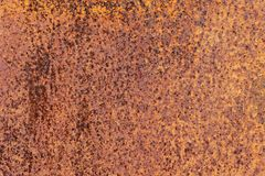 Rusty yellow-red textured metal surface. The texture of the metal sheet is prone to oxidation and corrosion. Grunge. Rusty yellow-red textured metal surface. The Stock Photos