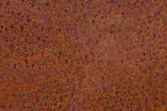 Rusty yellow-red textured metal surface. The texture of the metal sheet is prone to oxidation and corrosion. Grunge. Rusty yellow-red textured metal surface. The Royalty Free Stock Photo
