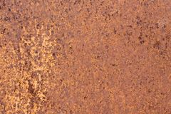 Rusty yellow-red textured metal surface. The texture of the metal sheet is prone to oxidation and corrosion. Grunge. Rusty yellow-red textured metal surface. The Stock Images