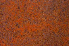Rusty yellow-red textured metal surface. The texture of the metal sheet is prone to oxidation and corrosion. Grunge. Rusty yellow-red textured metal surface. The Royalty Free Stock Images