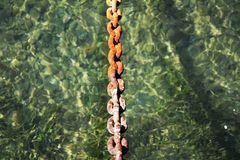 Rustying chain, blue trasparent water, natural background stock photos