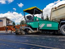 Ruszać się asfaltujący maszynerię na pracy zakończeniu up strzelał Obrazy Royalty Free